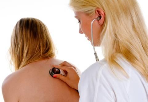 Lunginflammation läkare lyssnar på lungor hos kvinna